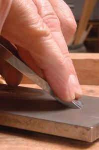 Une manière de supprimer les irrégularités d'un tranchant d'outil est d'en passer l'extrémité sur une pierre fine ou à eau. Certains artisans entraînés le font à main levée, en faisant basculer l'outil jusqu'à ce que l'extrémité du biseau vienne en contact avec la pierre. Ils déplacent ensuite l'outil d'un bout à l'autre de la pierre tout en conservant une inclinaison constante.